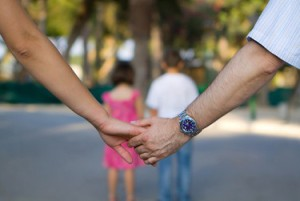 Couple holding hands while their children walk in front of them.