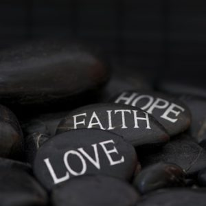 "Black pebble with engraved message ""love, faith, hope."""