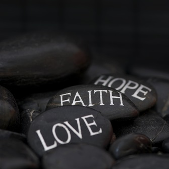"""Black pebble with engraved message """"love, faith, hope."""""""