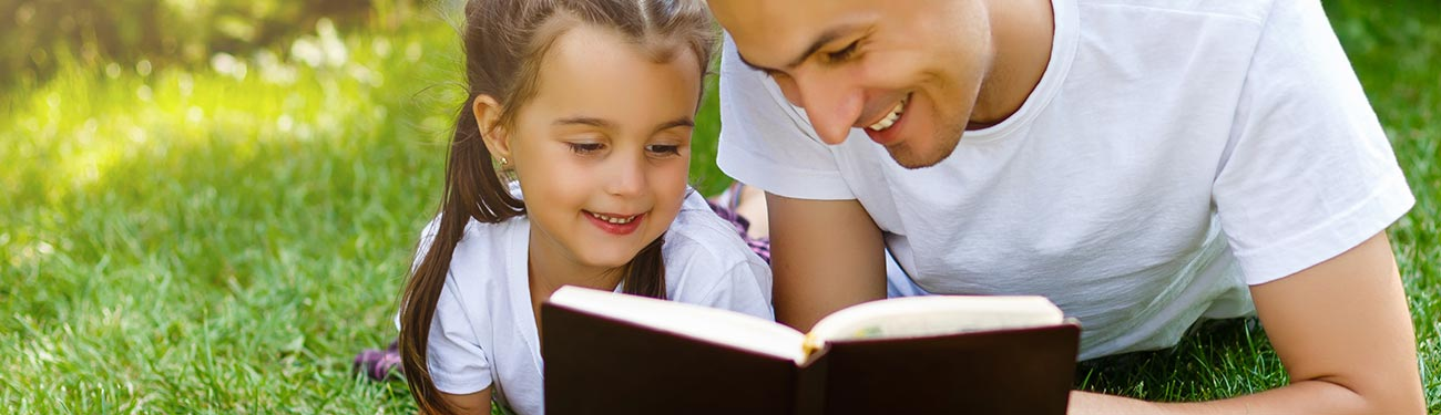 Father reading with daughter in grass