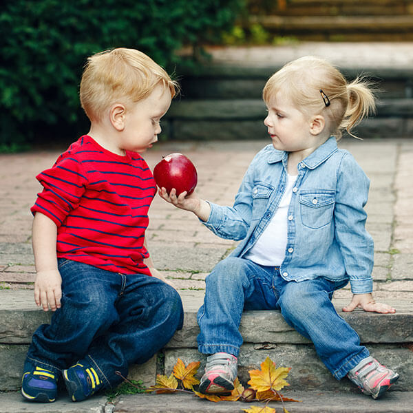 Little girl offering apple to little boy