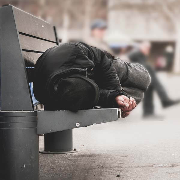 Homeless person asleep on bench