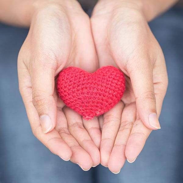 Hands holding out small knit heart