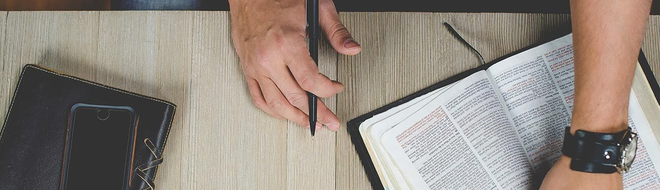 Man holding open bible with pen in hand