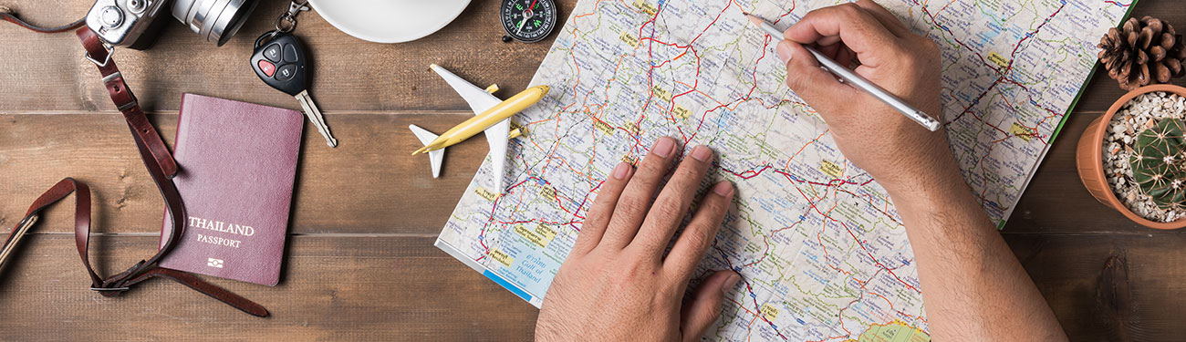Hand with pencil looking at travel map