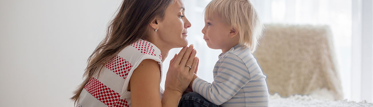 Woman holding child closely with hands together in prayer