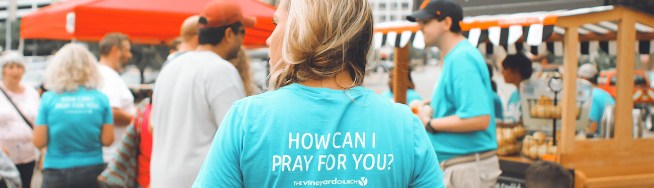Volunteer at church festival wearing shirt with text 'How can I pray for you?'