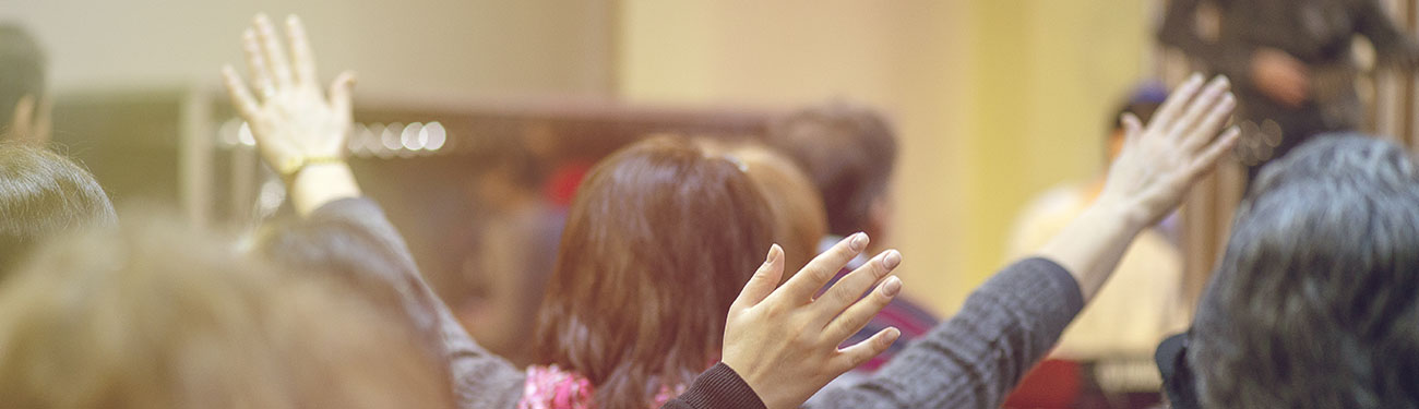 Church memebers worshiping with hands in the air