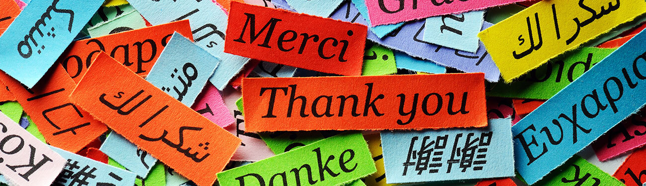 The word thank you on color pieces of paper in multiple languages