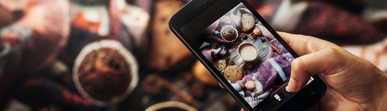 person taking picture with smartphone of food