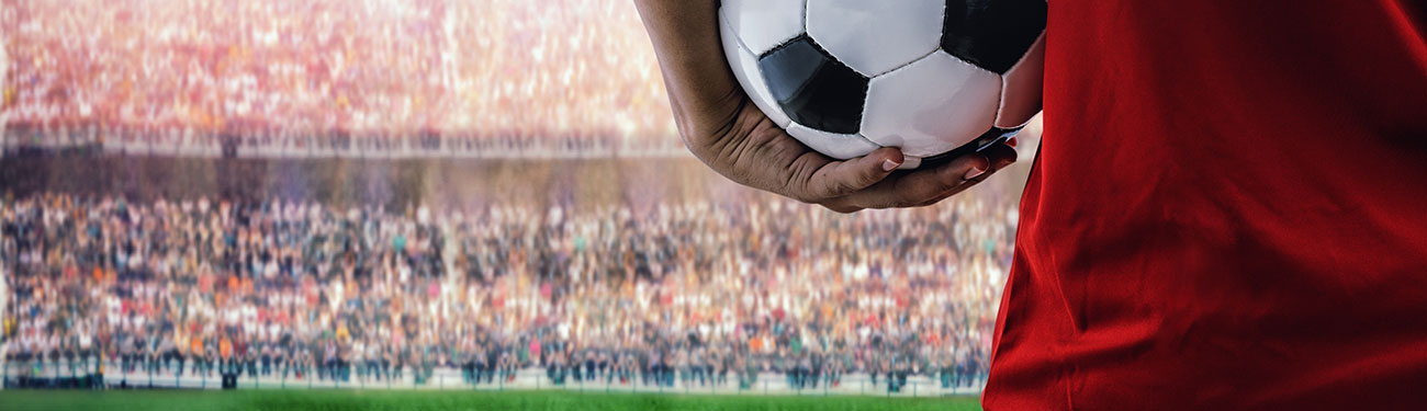 soccer playing holding a ball in stadium full of fans