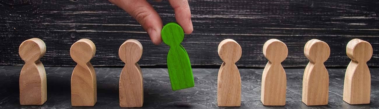 Finger picking up one wooden person in a group of wooden people