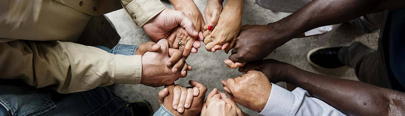 group of people holding hands in circle