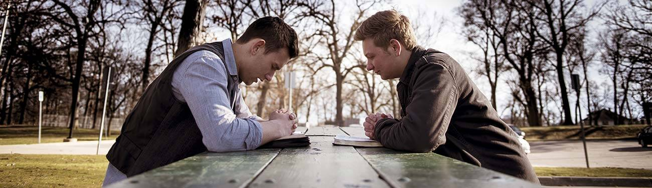 Two men praying outside on a picnic table